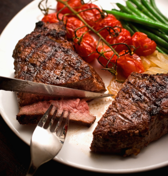 Organic Grass Fed Beef Steak cut with knife and fork