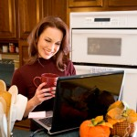 mom with coffee in the kitchen smiling at laptop